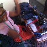 One of the seamstresses at HPCD's Cite Soleil incubator. Caught her during this joyous moment.