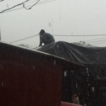 This guy sat on top of the truck while it was raining so he could empty the puddles forming on top of the truck bed's tarp.